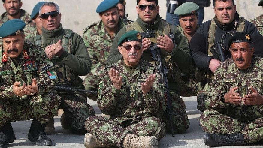 In this Monday, Feb. 24, 2014 photo, Afghanistan's chief of army Sher Mohammad Karimi, center, prays during a visit Afghanistan's National Army soldiers in Kunar province, Afghanistan. The Afghan government announced its full list of Cabinet nominees Monday, Jan. 12, 2015 after months of delays and missed deadlines. Karimi has been nominated for Defense Minister in Afghanistan's new cabinet. All cabinet nominees must now receive approval from the parliament. (AP Photo/Massoud Hossaini)