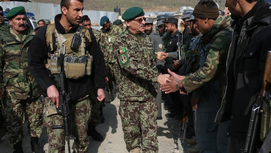 In this Monday, Feb. 24, 2014 photo, Afghanistan's chief of army Sher Mohammad Karimi, center, visits Afghanistan's National Army soldiers in Kunar province, Afghanistan. The Afghan government announced its full list of Cabinet nominees Monday, Jan. 12, 2015 after months of delays and missed deadlines. Karimi has been nominated for Defense Minister in Afghanistan's new cabinet. All cabinet nominees must now receive approval from the parliament. (AP Photo/Massoud Hossaini)