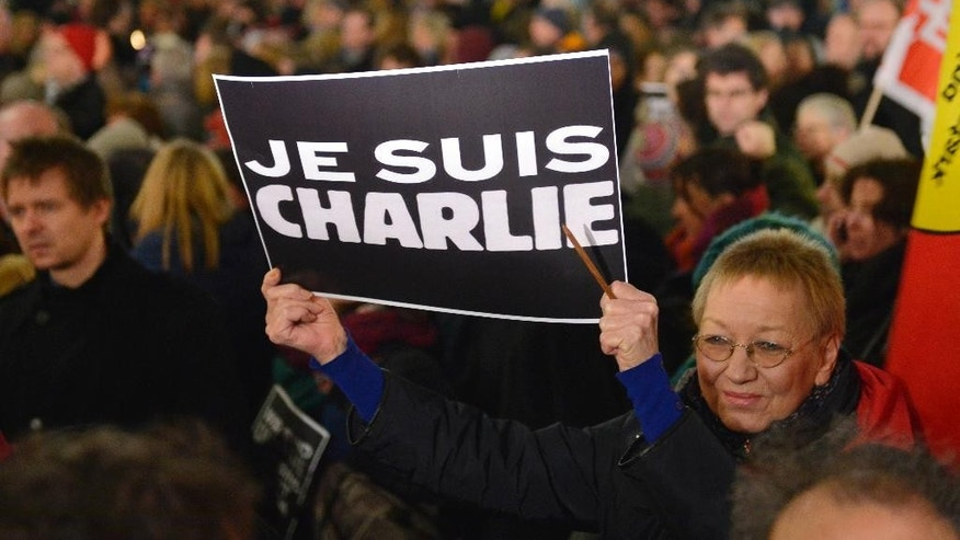"A woman shows a banner reading ""I am Charlie"" for the victims of the shooting at the satirical newspaper Charlie Hebdo in Paris during a demonstration of thousands against the right wing PEGIDA movement, 'Patriotic Europeans against the Islamization of the West' in Duesseldorf, Germany, Monday evening, Jan. 12, 2015.  (AP Photo/Martin Meissner)"