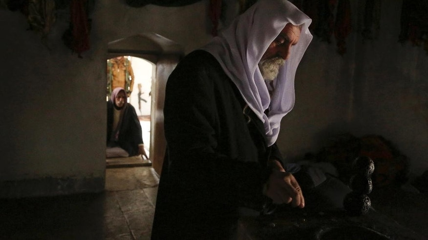 In this Sunday Jan. 11, 2015 photo, Yazidi priest Sheikh Ismael Bahri makes a silent wish and stacks three round stones inside the Sharaf al-Deen temple shrine, one of the holiest for the Yazidis, in Sinjar, northern Iraq. So long as they don't fall over, believers say the wish will come true, war or no war. The Yazdis are a religious minority whom the Islamic State group considers heretics ripe for slaughter. The shrine came under attack at least 16 times during the Islamic State onslaught, local fighters say, but the Yazidis held the line with help from Kurdish peshmerga forces who supplied weapons. (AP Photo/Seivan Selim)
