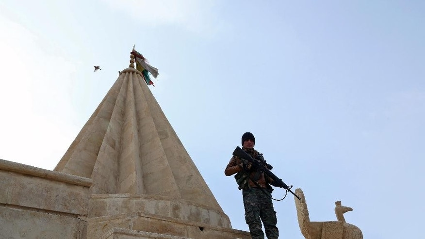 In this Sunday Jan. 11, 2015 photo,  a Yazidi fighters protects the Sharaf al-Deen temple shrine, one of the holiest for the Yazidis, a religious minority whom the Islamic State group considers heretics ripe for slaughter, in Sinjar, northern Iraq. Kurdish forces have taken back a large part of Sinjar since the Sunni extremists occupied it in August last year. The shrine came under attack at least 16 times during the Islamic State onslaught, local fighters say, but the Yazidis held the line with help from Kurdish peshmerga forces who supplied weapons. (AP Photo/Seivan Selim)