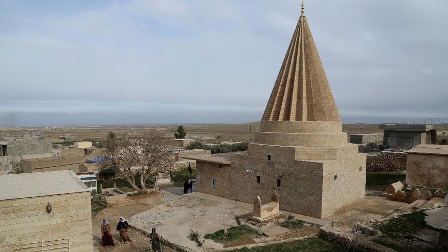 In this Sunday January. 11, 2015 photo,  people visit the Sharaf al-Deen temple shrine, one of the holiest for the Yazidis, a religious minority whom the Islamic State group considers heretics ripe for slaughter, in Sinjar, northern Iraq. Kurdish forces have taken back a large part of Sinjar since the Sunni extremists occupied it in August last year. The shrine came under attack at least 16 times during the Islamic State onslaught, local fighters say, but the Yazidis held the line with help from Kurdish peshmerga forces who supplied weapons. (AP Photo/Seivan Selim)
