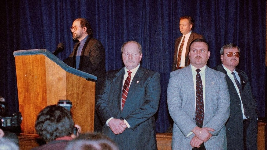 "FILE - In this file photo dated Dec. 11, 1991, security guards surround author Salman Rushdie, left, as he addresses an audience at Columbia University's Low Library, in his first public appearance outside of England since Iran issued a fatwa calling for his death over his novel ""The Satanic Verses.""  The slaughter of ten journalists and two policemen on Jan. 7, 2015,  at the offices of satirical French newspaper Charlie Hebdo that mocked politicians and prelates with equal glee is grim evidence that humor can be dangerous, another bloody chapter in a story that stretches back to Rushdie's 1988 novel ""The Satanic Verses,"" whose comic take on the prophet drew a death edict from Iran's religious authorities. (AP Photo/Mark Lennihan, FILE)"