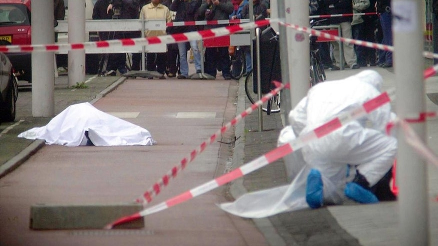 FILE- In this file photo dated Tuesday, Nov. 2, 2004, the covered body of Theo van Gogh is seen at left while forensic experts investigate the scene of his murder in Amsterdam, after filmmaker Van Gogh received death threats after making a movie criticizing the treatment of women under Islam. A Muslim fanatic angered by the documentarist's depiction of Islam is just one incident in the clash of cultures which erupted with the slaughter of ten journalists and two policemen on Jan. 7, 2015, at the offices of satirical French newspaper Charlie Hebdo that mocked politicians and prelates with equal glee. (AP Photos/Eran Oppenheimer, FILE) NETHERLANDS OUT