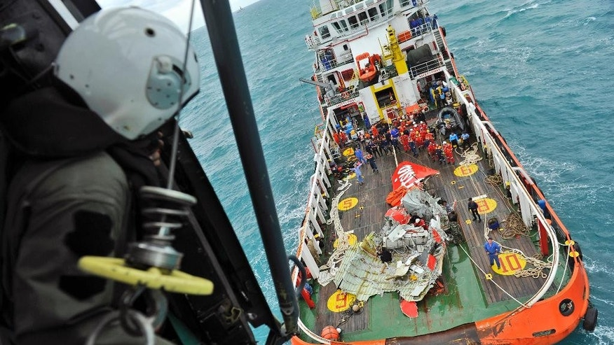 In this photo taken from an Indonesian Air Force Super Puma helicopter Saturday, Jan. 10, 2015, portion of the tail of AirAsia Flight 8501 is seen on the deck of a rescue ship after it was recovered from the sea floor on the Java Sea. Investigators searching for the crashed AirAsia plane's black boxes lifted the tail portion of the jet out of the Java Sea on Saturday, two weeks after it went down, killing all 162 people on board. (AP Photo/Prasetyo Utomo, Pool)