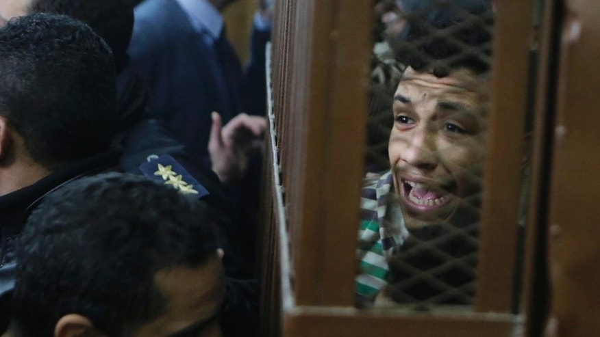 Some of 26 men, who were arrested in a televised raid last month by police looking for gays at a Cairo public bathhouse, react after an Egyptian court acquitted them in Cairo, Egypt, Monday, Jan. 12, 2015. The trial, which had caused an uproar among activists and rights groups, captured public attention after a pro-government TV network aired scenes of half-naked men being pulled from the bathhouse by police.(AP Photo/Amr Nabil)