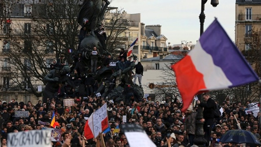 Jan. 11, 2015: People wave national flags and hold placards that read 'I am Charlie' at the Place de la Nation in Paris. (AP Photo/Burhan Ozbilici)