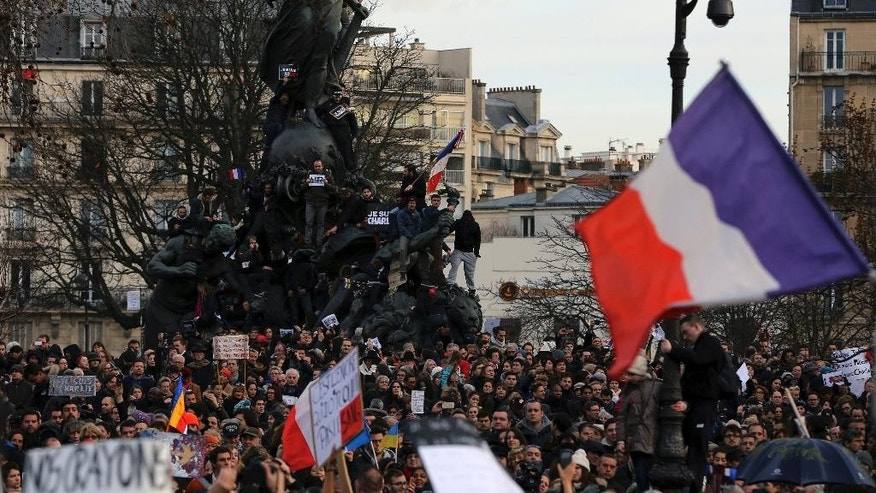 "People wave national flags and hold placards that read ""I am Charlie"" at the Place de la Nation in Paris, France, Sunday, Jan. 11, 2015. More than 40 world leaders, their arms linked, marched through Paris Sunday to rally for unity and freedom of expression and to honor 17 victims of three days of terrorist attacks. (AP Photo/Burhan Ozbilici)"