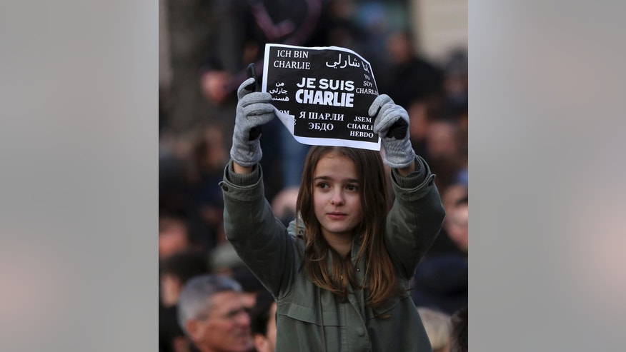 "A girl holds up a placard that reads ""I am Charlie"" in several languages at the Place de la Nation in Paris Sunday, Jan. 11, 2015. More than 40 world leaders, their arms linked, marched through Paris Sunday to rally for unity and freedom of expression and to honor 17 victims of three days of terrorist attacks. (AP Photo/Burhan Ozbilici)"