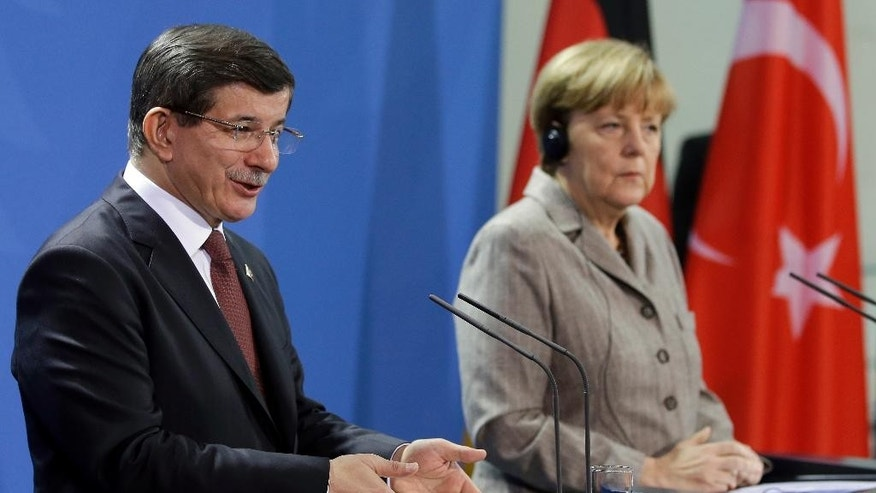 German Chancellor Angela Merkel, right, and the Prime Minister of Turkey Ahmet Davutoglu address the media during a joint press conference after a meeting at the chancellery in Berlin, Germany, Monday, Jan. 12, 2015. (AP Photo/Michael Sohn)