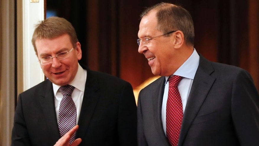 Russian Foreign Minister Sergey Lavrov, right, welcomes his Latvian counterpart Edgars Rinkevics during their talks in Moscow, Russia, Monday, Jan. 12, 2015. Lavrov is scheduled to meet four of his colleagues from the Normandy group in Berlin later today to discuss preparations for upcoming meeting of their country leader's in an attempt to settle the crisis in Ukraine. (AP Photo/Pavel Golovkin)