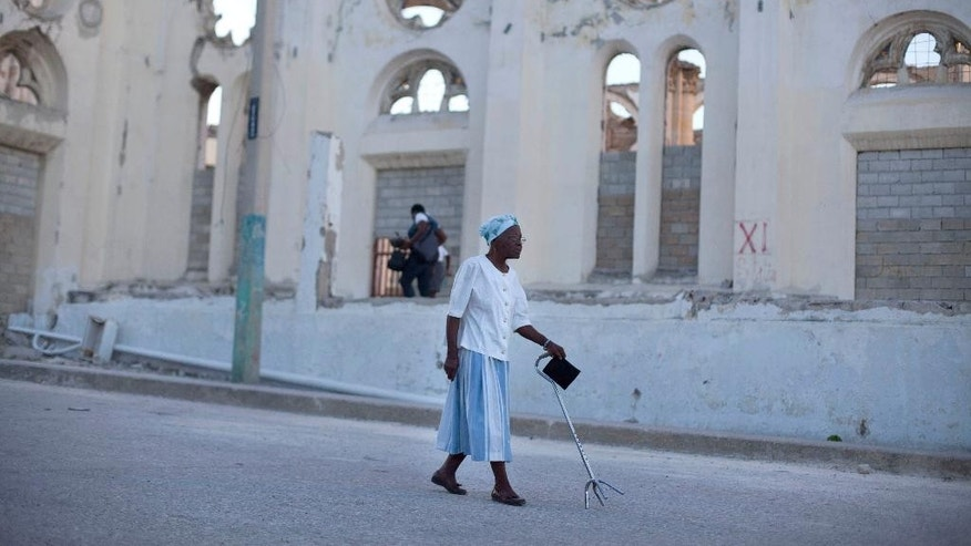 A woman walks past the ruins of the National Cathedral during the 5th anniversary of the Janaury 2010 earthquake in Port-au-Prince, Haiti, Monday, Jan. 12, 2015. Somber Haitians gathered early Monday to remember the devastating earthquake that left much of the capital and surrounding area in ruins in one of the worst natural disasters of modern times. ( AP Photo/Dieu Nalio Chery)