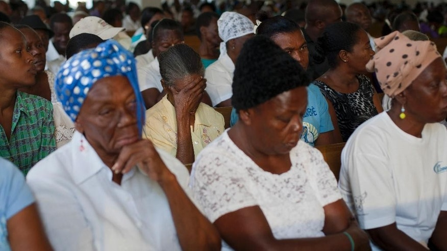Haitians attend a Mass marking the 5th anniversary of the January 2010 earthquake, in a new building next to the ruins of the National Cathedral in Port-au-Prince, Haiti, Monday, Jan. 12, 2015. Somber Haitians gathered early Monday to remember the devastating earthquake that left much of the capital and surrounding area in ruins in one of the worst natural disasters of modern times. ( AP Photo/Dieu Nalio Chery)