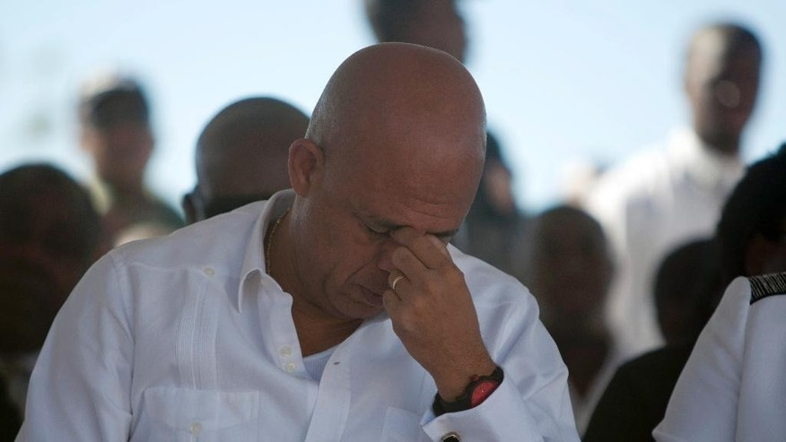 Haiti's President Michel Martelly attends a memorial service for victims of the January 2010 earthquake, at Titanyen, a mass burial site north of Port-au-Prince, Haiti, Monday, Jan. 12, 2015. Somber Haitians gathered early Monday to remember the devastating earthquake that left much of the capital and surrounding area in ruins in one of the worst natural disasters of modern times. ( AP Photo/Dieu Nalio Chery)