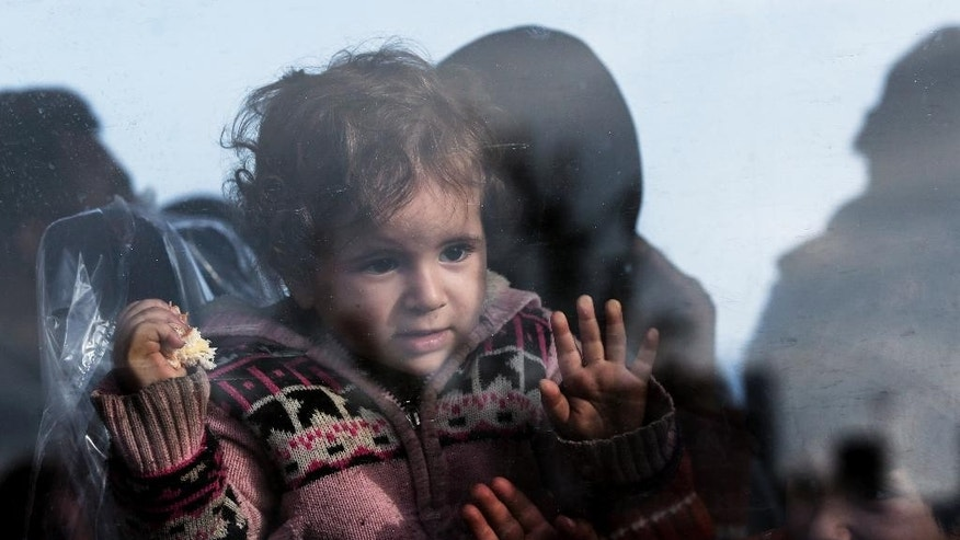 In this Nov. 27, 2014 file photo, a baby looks out from the window of a bus after disembarking from a crippled freighter carrying hundreds of refugees trying to migrate to Europe, at the coastal Cretan port of Ierapetra, Greece. Migrants dreaming of Europe have their pick of social media sites that work like an online travel agent, advertising fares and offering tips on secure payments. Meanwhile, the traffickers who send them floating across the Mediterranean are buying scrapyard cargo ships over the Internet. (AP Photo/Petros Giannakouris, File)