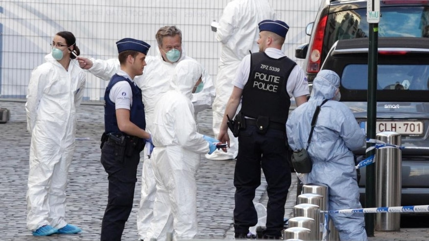 FILE - In this May 24, 2014 file photo, forensic experts examine the site of a shooting at the Jewish Museum in Brussels. A Frenchman linked to the Islamic State group in Syria crossed into Belgium and killed four people at the museum. The threat of Islamic extremism has justice officials balancing tougher law enforcement against the need to protect civil liberties, and that balance is struck in myriad ways around the world. (AP Photo/Yves Logghe, File)