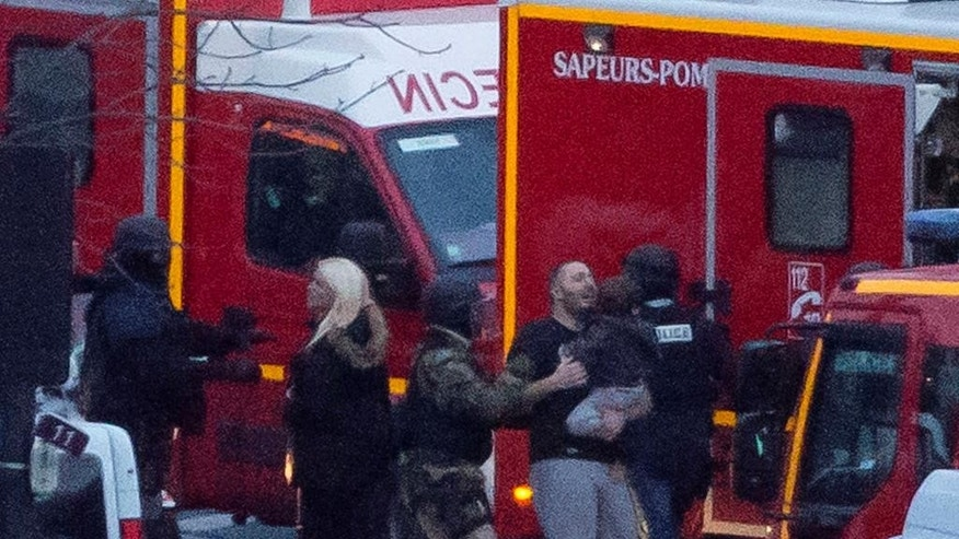 FILE - This is a Friday, Jan. 9, 2015 file photo of a security officer as he directs released hostages after they stormed a kosher market to end a hostage situation, Paris. Explosions and gunshots were heard as police forces stormed a kosher grocery in Paris where a gunman was holding at least five people hostage. The killing of four French Jews in last week's hostage standoff at a Paris kosher market has deepened the fears among European Jewish communities shaken by rising anti-Semitism and feeling vulnerable by poor security and a large number of potential soft targets. (AP Photo/Michel Euler, File)