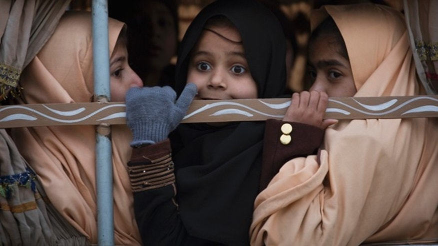 Jan. 12, 2015: Pakistani students look out from a vehicle on their way to school near the Army Public School which was targeted by Taliban militants last year, in Peshawar. (AP Photo/B.K. Bangash)