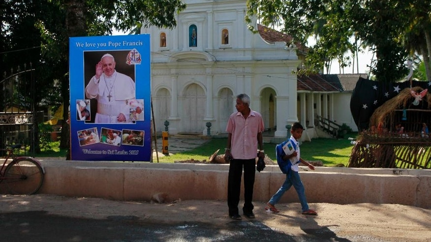 FILE - In this Tuesday, Jan. 6, 2015 file photo, Sri Lankans walk past a poster to welcome Pope Francis outside a church in Moratuwa, on the outskirts of Colombo, Sri Lanka. Less than a week after its longtime president was surprisingly voted out of office, Sri Lanka welcomes Pope Francis on Tuesday, with the island nation's Catholic minority hoping he can help heal the lingering wounds of the country's 25-year civil war. (AP Photo/Eranga Jayawardena, File)