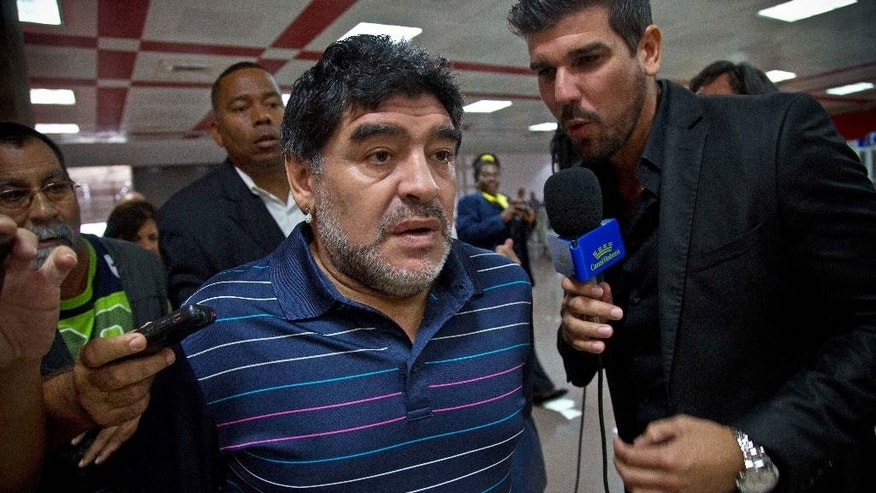 Argentina's soccer legend Diego Armando Maradona talks to journalist at the airport on his way to catch a departing plane in Havana, Cuba, Monday, Jan. 12, 2015. Fidel Castro on Monday sent Maradona a letter written to quash rumors of the Cuban leader's death, state-run television network Telesur reported. It was the first reported word from Castro in nearly three months. The network showed photos of Maradona with the letter signed by Castro, 88. Telesur revealed nothing about the contents of the letter, but said it rebutted rumors he had died. (AP Photo/Ramon Espinosa)