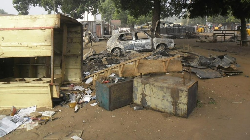 A child, at rear, walks through the scene of an explosion in a mobile phone market in Potiskum, Nigeria, Monday Jan. 12, 2015. Two female suicide bombers targeted the busy marketplace on Sunday. (AP Photo/Adamu Adamu)