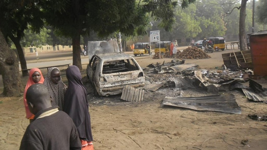 Children stand near the scene of an explosion in a mobile phone market in Potiskum, Nigeria, Monday Jan. 12, 2015. Two female suicide bombers targeted the busy marketplace on Sunday. (AP Photo/Adamu Adamu)