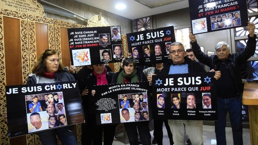 "French Israelis hold signs with pictures of French Jewish victims of last week's attack on a Paris Kosher supermarket with writing that reads,  ""I Am Charlie"" and ""I am dead because I am Jewish"" prior to a prayer at a French synagogue, in the port city of Ashdod, Israel, Monday, Jan. 12, 2015. (AP Photo/Tsafrir Abayov)"