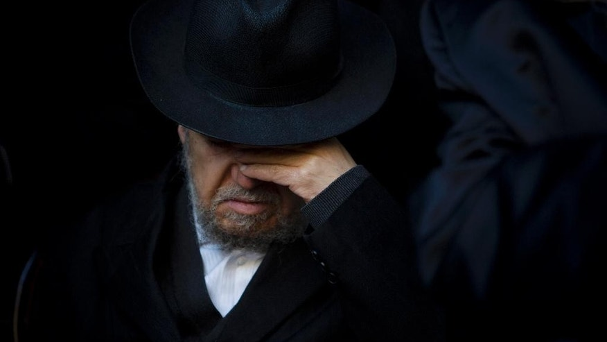 A relative of French Jew Yoav Hattab, a victim of the attack on kosher grocery store in Paris, attends his funeral procession in the city of Bnei Brak near Tel Aviv, Israel, Tuesday, Jan. 13, 2015. Israel geared up on Tuesday for the solemn funerals of four Jewish victims of a Paris terror attack on a kosher supermarket amid rising concerns over increased anti-Semitism in Europe. Hattab will be buried in Jerusalem with the other victims. (AP Photo/Oded Balilty)