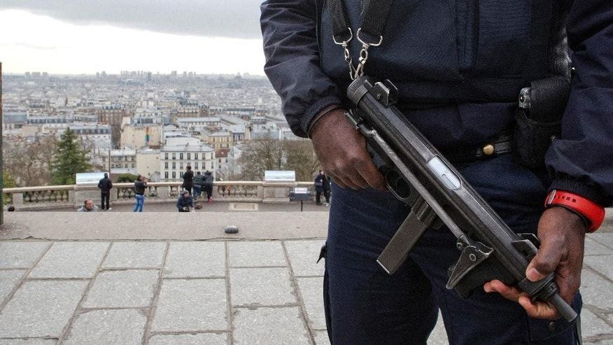 A French police officer patrols around the Sacre Coeur basilica at Montmartre district, in Paris, Monday, Jan. 12, 2015. France on Monday ordered 10,000 troops into the streets to protect sensitive sites after three days of bloodshed and terror, amid the hunt for accomplices to the attacks that left 17 people and the three gunmen dead. (AP Photo/Jacques Brinon)
