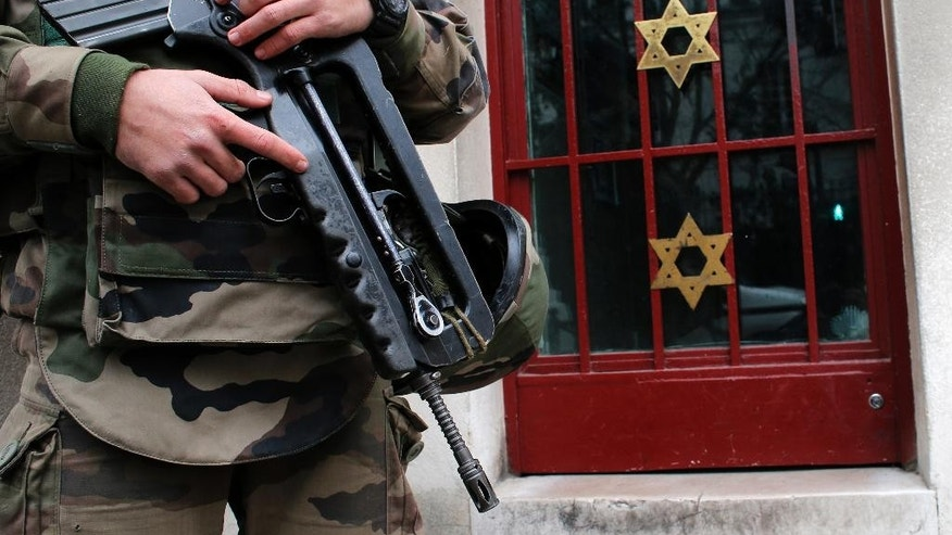 A soldier stands guard outside a synagogue in Neuilly sur Seine, outside, Paris, France, Tuesday, Jan. 13, 2015. France on Monday ordered 10,000 troops into the streets to protect sensitive sites after three days of bloodshed and terror, amid the hunt for accomplices to the attacks that left 17 people and the three gunmen dead. (AP Photo/Christophe Ena)