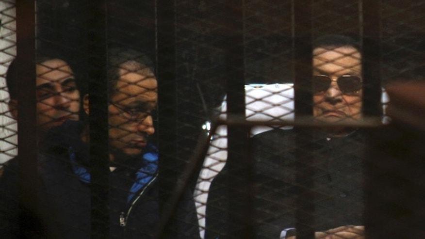 Nov. 29, 2014: In this file photo, ousted Egyptian President Hosni Mubarak, 86, lies on a gurney, next to his son Gamal, second left, in the defendants cage, during a court hearing in Cairo, Egypt.