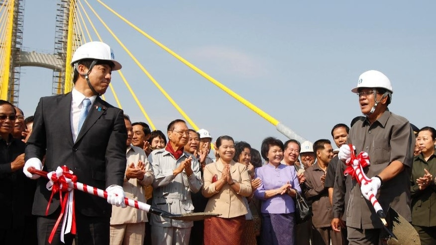 Cambodia's Prime Minister Hun Sen, right, stands with Kazuyuki Nakane, left, Japanese Parliamentary Vice-Minister for Foreign Affairs, during a ceremony inaugurating the country's longest bridge in Neak Loeung,  southeast of Phnom Penh, Cambodia, Wednesday, Jan. 14, 2015. Hun Sen, Cambodia's tough and wily prime minister, marks 30 years in power Wednesday, one of only a handful of political strongmen worldwide who have managed to cling to their posts for three decades. (AP Photo/Heng Sinith)