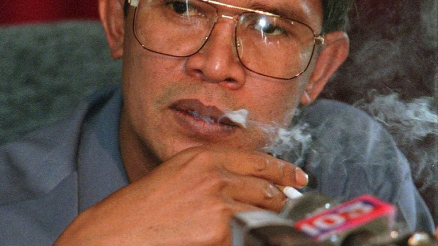 In this April 19, 1997 file photo, then Cambodian Second Prime Minister Hun Sen smokes a cigarette during a news conference held in his compound at Takhamao, south of Phnom Penh, Cambodia. Hun Sen, Cambodia's tough and wily prime minister, marked 30 years in power Wednesday, January 14, 2015, one of only a handful of political strongmen worldwide who have managed to cling to their posts for three decades. (AP Photo/Charles Dharapak, File)