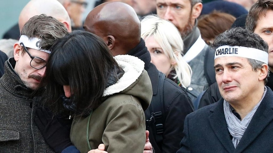 FILE – In this Sunday, Jan. 11, 2015, file photo, Charlie Hebdo newspaper staff, with editorialist Patrick Pelloux, right, cartoonist Renald Luzier, known as Luz, left, grieve during a rally in Paris. Over a million people, including more than 40 world leaders, streamed into the heart of Paris for a rally of national unity, days after the attacks on the satirical magazine Charlie Hebdo, police officers and a kosher grocery. (AP Photo/Michel Euler, File)