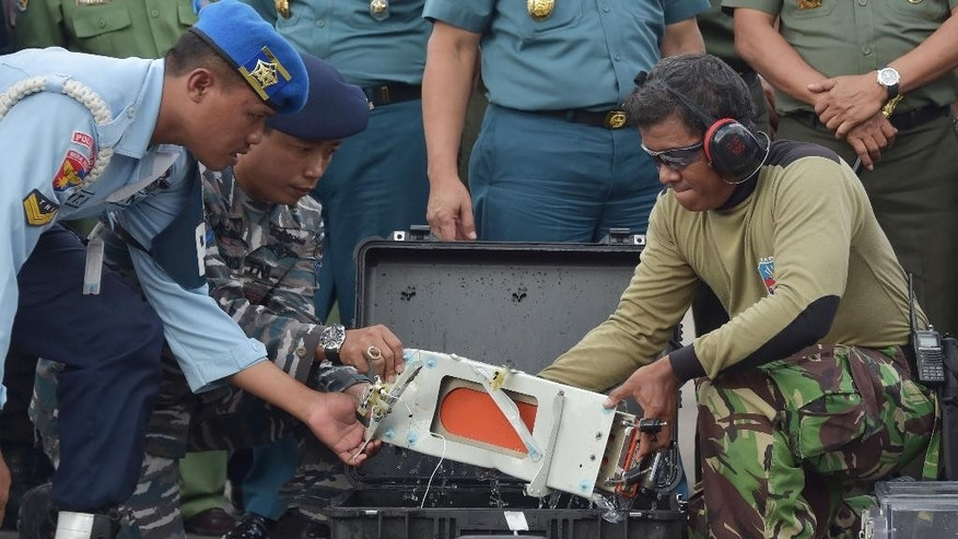 Indonesian air force personnel push an Air Force NAS 332 Super Puma helicopter before they begin a seach operation  of the ill-fated AirAsia Flight 8501 crashed off the Java Sea, at an airport in Pangkalan Bun, Indonesia, Tuesday, Jan. 13, 2015. (AP Photo/Achmad Ibrahim)