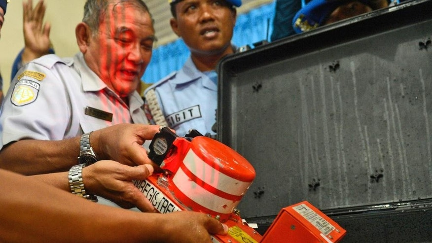 Head of Indonesian National Transportation Safety Committee Tatang Kurniadi, center, shows, the newly recovered Cockpit Voice Recorder from the ill-fated AirAsia Flight 8501 during a press conference in Pangkalan Bun, Central Borneo, Indonesia, Tuesday, Jan. 13, 2015.  Divers retrieved the crashed AirAsia plane's second black box from the bottom of the Java Sea on Tuesday, giving experts essential tools to piece together what brought Flight 8501 down. (AP Photo)