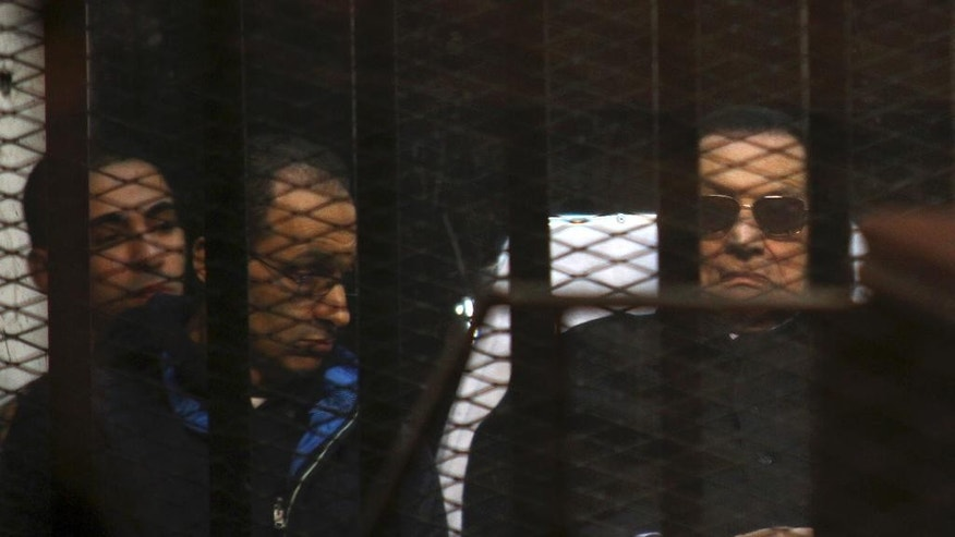 FILE - In this Nov. 29, 2014 file photo, ousted Egyptian President Hosni Mubarak, 86, lies on a gurney, next to his son Gamal, second left, in the defendants cage, during a court hearing in Cairo, Egypt. Egypt's top appeals court has ordered the retrial of the deposed president and his two sons in a corruption case, a move that could pave the way for the former autocrat's release. The Appeals Court announced its ruling in a brief session Tuesday, Jan. 13, 2015, carried live on several Egyptian TV networks. (AP Photo/Tarek el-Gabbas, File)