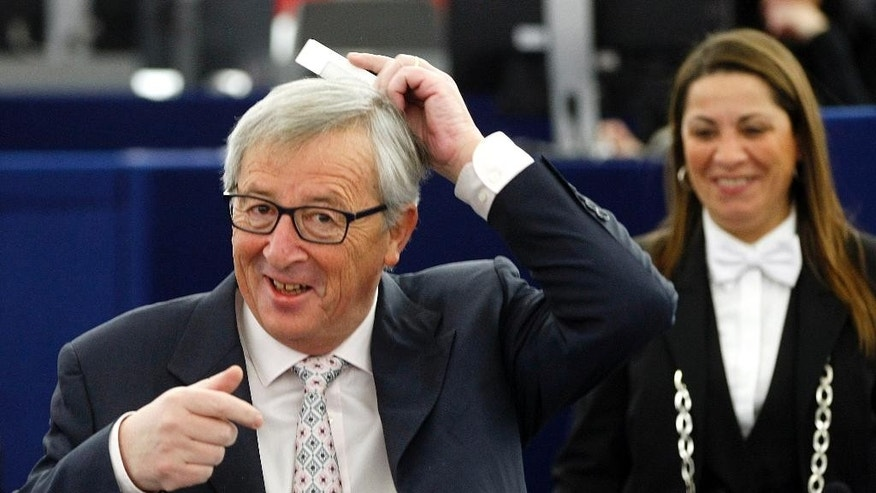 President of the European Commission Jean-Claude Juncker combs his hair as a joke for photographers Tuesday Jan. 13, 2015 at the European Parliament in Strasbourg, eastern France, after Italian Prime Minister Matteo Renzi reviewed the outgoing EU presidency. (AP Photo/Christian Lutz)