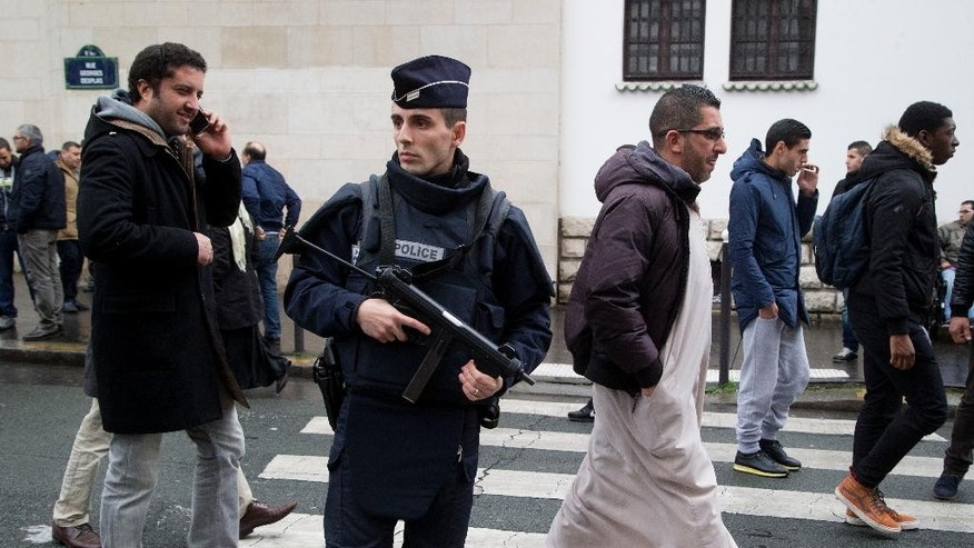 Jan. 9, 2015: A French police officer stands guard outside the Grand Mosque as people arrive for Friday prayers in Paris.