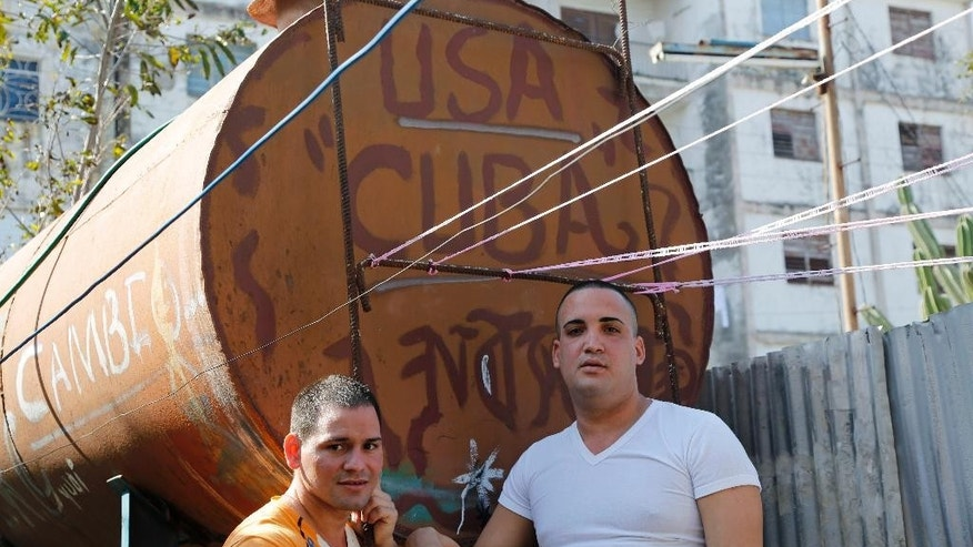 Freed Cuban dissidents Reinier Mulet, left, and Miguel Alberto Ulloa, stand beside a water tank in Havana, Cuba, Tuesday, Jan. 13, 2015. Ulloa and Mulet are two of 53 dissidents freed, most in the last week, as part of a U.S.-Cuban deal that also saw both countries liberate high-profile prisoners charged with espionage and move to normalize relations after five decades of tension. (AP Photo/Desmond Boylan)
