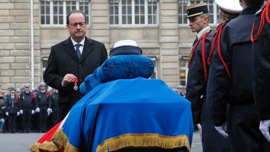 French President Francois Hollande holds a medal in front of the coffin of Police officer Clarissa Jean-Philippe during a ceremony to pay tribute to the three police officers killed in the attacks, in Paris, France, Tuesday, Jan. 13, 2015.  Clarissa Jean Philippe was killed by Ahmed Coulibaly last week in Paris. (AP Photo/Francois Mori, pool)