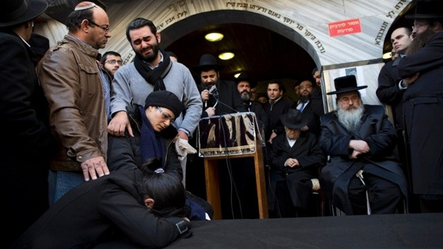 Jan. 13, 2015: Family and relatives of French Jew Yoav Hattab, a victim of the attack on a kosher grocery store in Paris, gather around a symbolic coffin for his funeral procession in the city of Bnei Brak near Tel Aviv. (AP Photo/Oded Balilty)