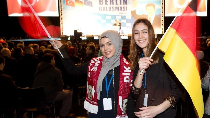 Two girls wave a Turkish and a German flag during a speech of Turkish Prime Minister Ahmet Davutoglu in Berlin Monday, Jan. 12, 2015. (AP Photo/dpa, Joerg Carstensen)