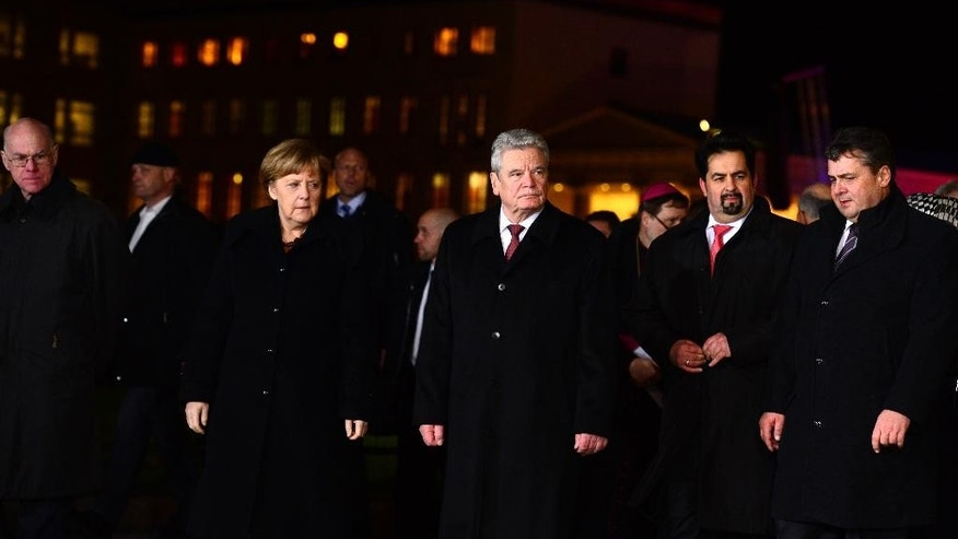 President of Bundestag Norbert Lammer, German Chancellor Angela Merkel, German President Joachim Gauck, the chairman of the Central Council of Muslims in Germany, Aiman Mazyek and German Vice Chancellor Sigmar Gabriel, from left, attend a vigil organized by the German Muslim Council to commemorate the victims of the Paris terror attacks, in front of the Brandenburg Gate near the French embassy in Berlin, Germany, Tuesday, Jan. 13, 2015. (AP Photo/John MacDougall, Pool)