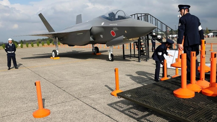 In this Oct. 26, 2014 photo, Japan Air Self Defense Force crew members set up cordons to protect a mock-up of the F-35 fighter jet during the annual Self-Defense Forces Commencement of Air Review at Hyakuri Air Base, north of Tokyo. Japan's Cabinet approved the country's largest ever defense budget on Wednesday, Jan. 14, 2015, including plans to buy surveillance aircraft, drones and F-35 fighter jets to help counter China's rising assertiveness in the region. (AP Photo/Eugene Hoshiko)