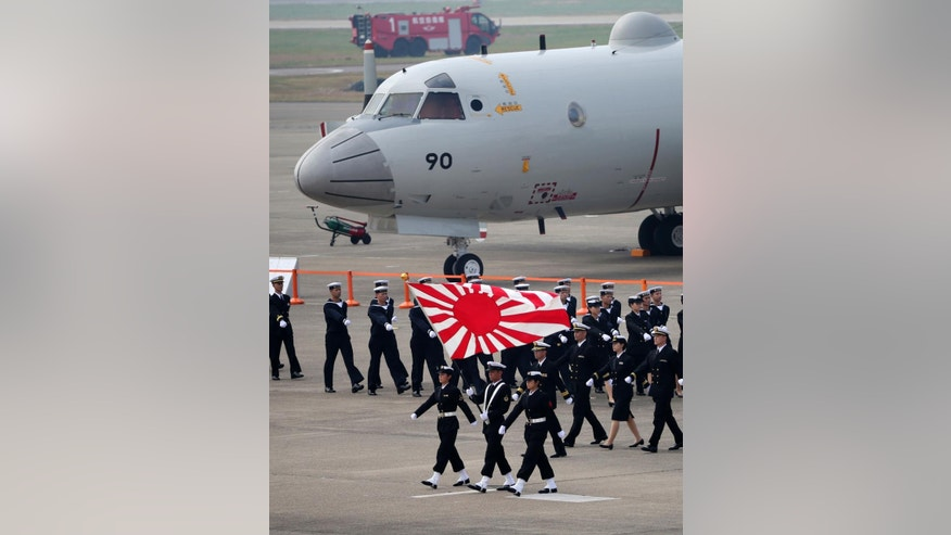 In this Oct. 26, 2014 photo, members of the Japan Self-Defense Forces march during the annual Self-Defense Forces Commencement of Air Review at Hyakuri Air Base, north of Tokyo. Japan's Cabinet approved the country's largest ever defense budget on Wednesday, Jan. 14, 2015, including plans to buy surveillance aircraft, drones and F-35 fighter jets to help counter China's rising assertiveness in the region. (AP Photo/Eugene Hoshiko)