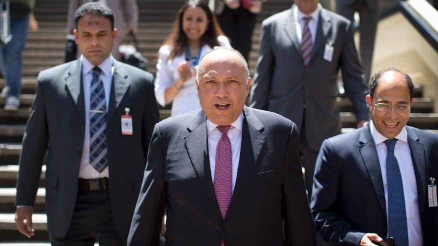 Egypt's Foreign Minister, Sameh Shukri, center, arrives for a reception where he was ambushed by a protest of journalists wearing black tape over their mouths to signify silencing of the media, over the continued detention of three Al-Jazeera English journalists in his country, as part of his visit to the United Nations Office in Nairobi, in Kenya Tuesday, Jan. 13, 2015. Media based in Nairobi, where detained Australian Al-Jazeera journalist Peter Greste is based, staged the protest while Shukri was visiting the UN office to speak about Egypt being a candidate for a non-permanent seat at the UN Security Council. (AP Photo/Ben Curtis)
