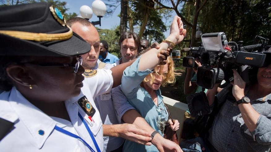 United Nations security staff eject journalists as they stage a protest about the continued detention of three Al-Jazeera English journalists in Egypt, during the visit of Egypt's Foreign Minister Sameh Shukri to the United Nations Office in Nairobi, in Kenya Tuesday, Jan. 13, 2015. Media based in Nairobi, where detained Australian Al-Jazeera journalist Peter Greste is based, staged the protest while Shukri was visiting the UN office to speak about Egypt being a candidate for a non-permanent seat at the UN Security Council. (AP Photo/Ben Curtis)