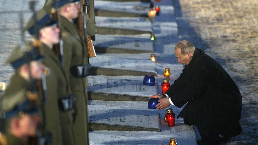 FILE - In this Thursday, Jan. 27, 2005 file photo, Russian President Vladimir Putin lights a candle during the ceremony marking the 60th anniversary of the liberation of the Auschwitz-Birkenau Nazi concentration camp by Soviet troops in Oswiecim, Poland. Putin will not travel to a ceremony in Poland marking the 70th anniversary of the liberation of the Nazis' Auschwitz death camp because he hasn't been invited by the hosts, the Kremlin said Tuesday Jan. 13, 2015. (AP Photo/Misha Japaridze, File)