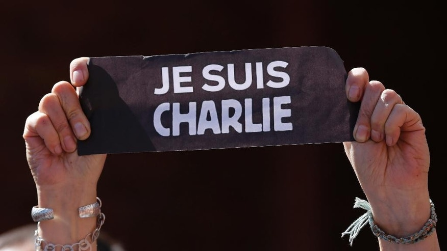 "Jan.11, 2015: A person holds a sign that reads in French ""I am Charlie"" during a gathering in solidarity with the victims of recent attacks in France at the French Alliance community center in Quito, Ecuador. (AP)"